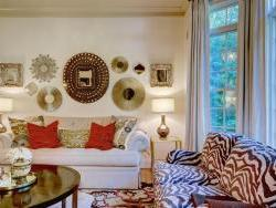 Detail of colletion of wall mirrors displayed. New loveseat upholstered in zebra fabric. New coffee table.