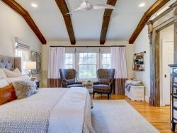 Paramus bedroom Neutral colors warmed with cognac accents wood beams and an antique inspired door surround